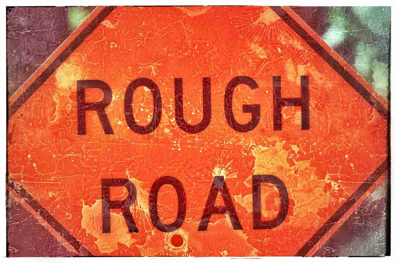 "A highway warning sign that says ""ROUGH ROAD."""