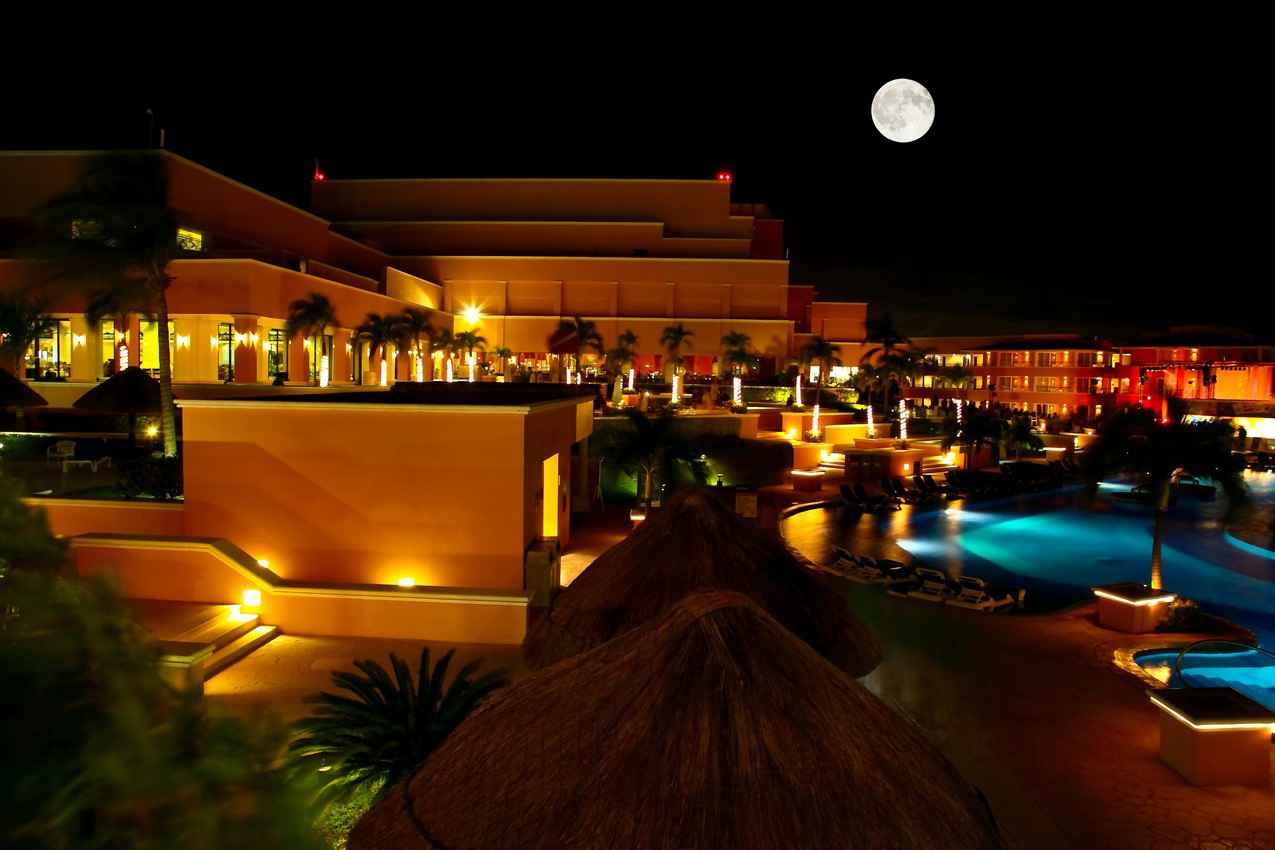 A full moon visible above a beautiful resort pool.