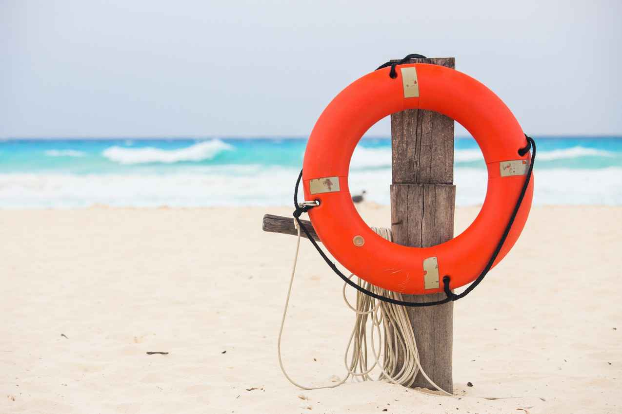 A white sand beach with a post holding an orange life preserver and a rope.