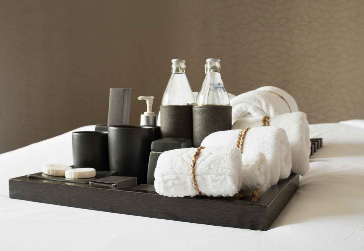 Several bath towels with washcloths and toiletries in a fancy bathroom.