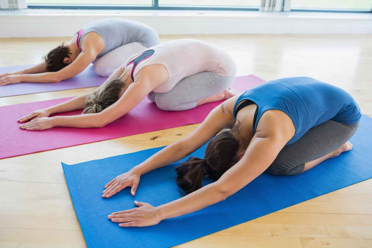 Three women doing yoga at a gym.