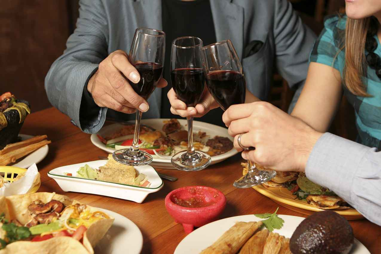 A family of three drinking wine with a traditional Mexican dinner.