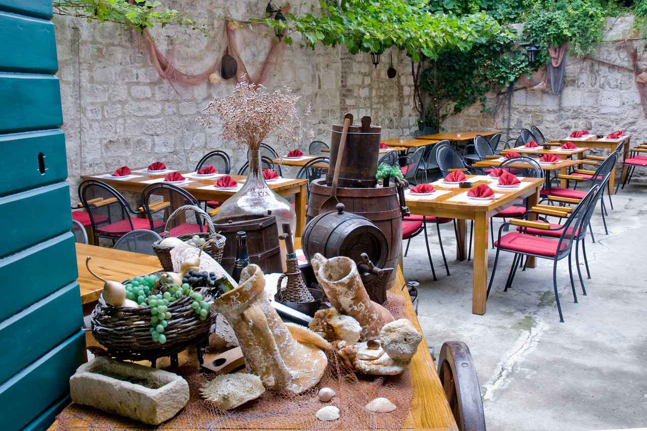 An outdoor restaurant with lots of seating and plants surrounding the dining area.