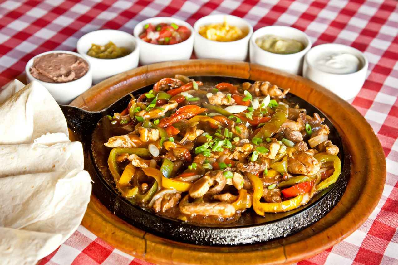 A skillet with fajita meat and vegetables next to a plane of tortillas and various toppings.