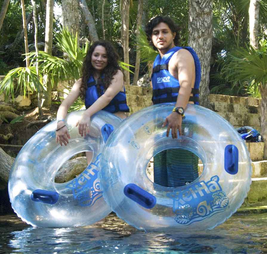 A man and a woman carrying several inflatable tubes at Xel-Ha park.