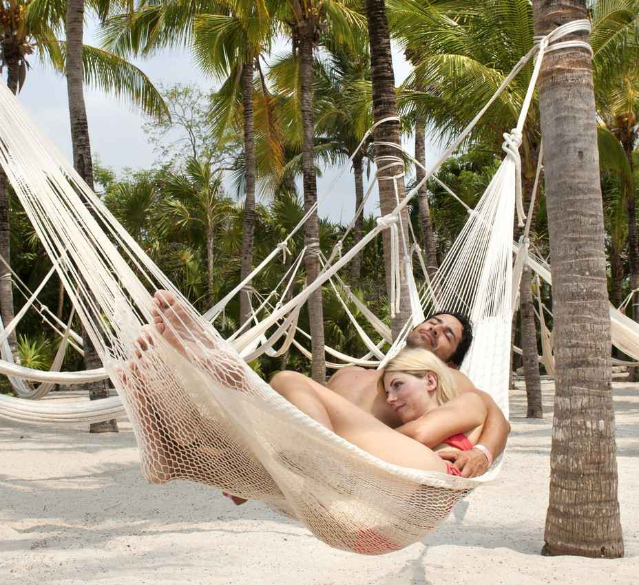 A man and a woman relaxing in a hammock on the beach.