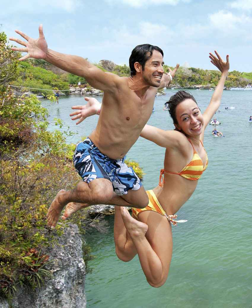 Two people jumping off a short cliff into the water near Playa Del Carmen.