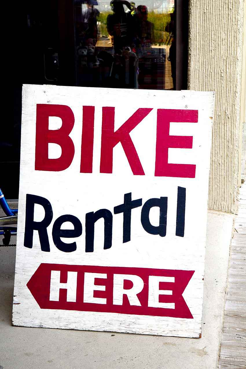 A wooden bike rental here sign.
