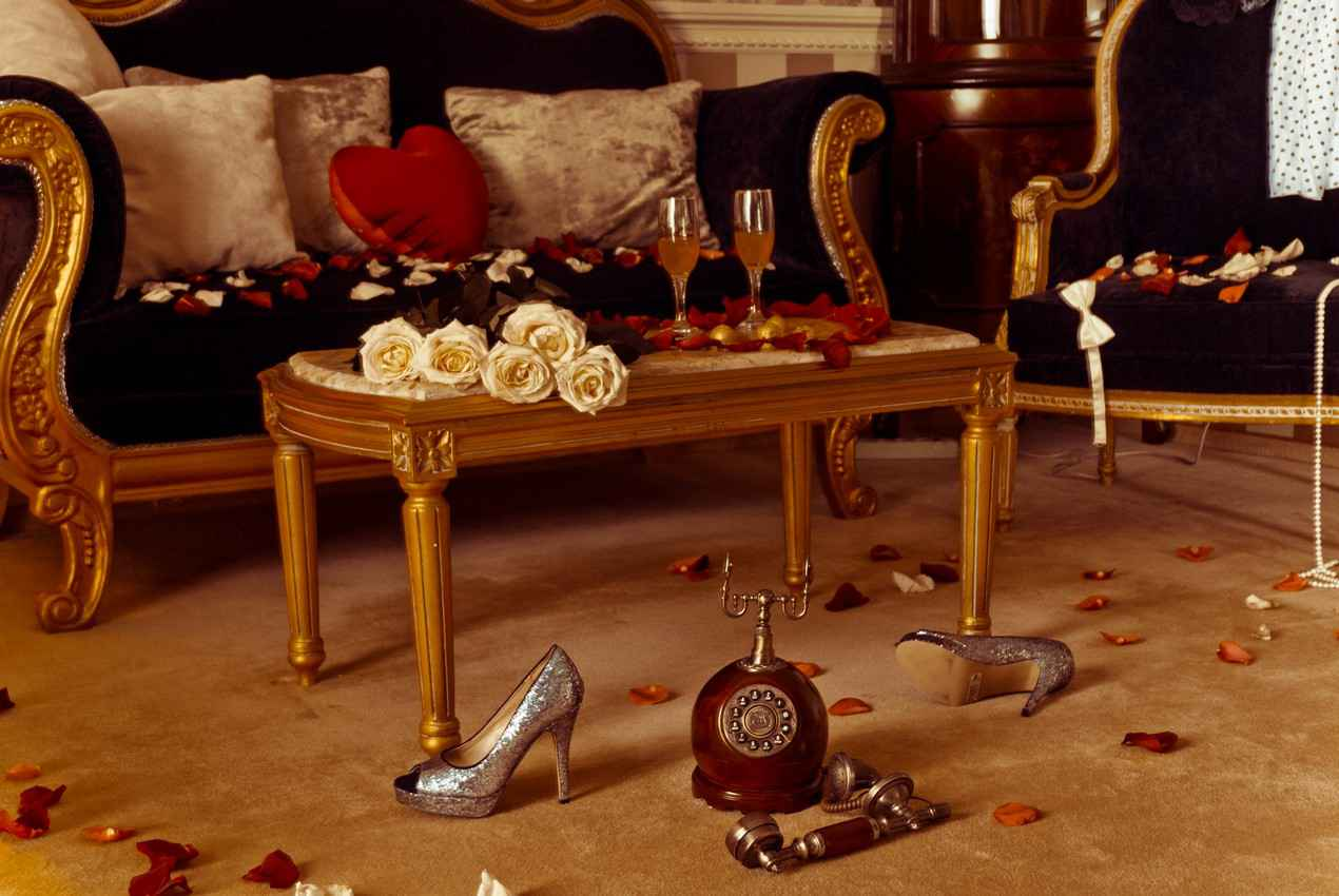 Flower petals strewn all around a room with champagne glasses in preparation for a romantic evening.