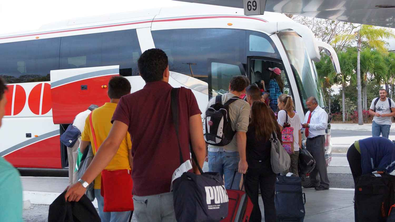 Several people boarding a transfer bus at the Cancun international Airport.