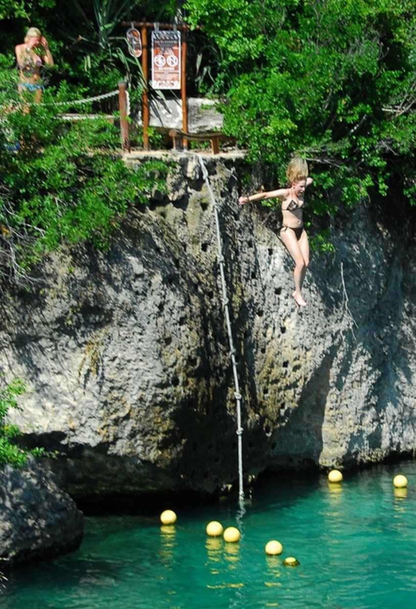 "Several people jumping from the ""Cliff of Courage"" above a local cenote."