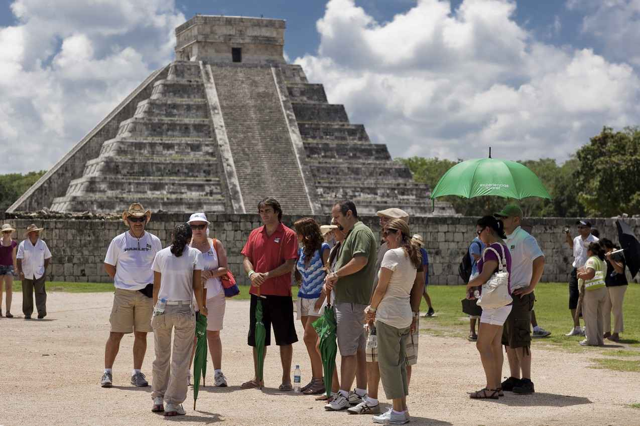 A group of tourists and a tour guide gathered in front of El Castillo pyramid.