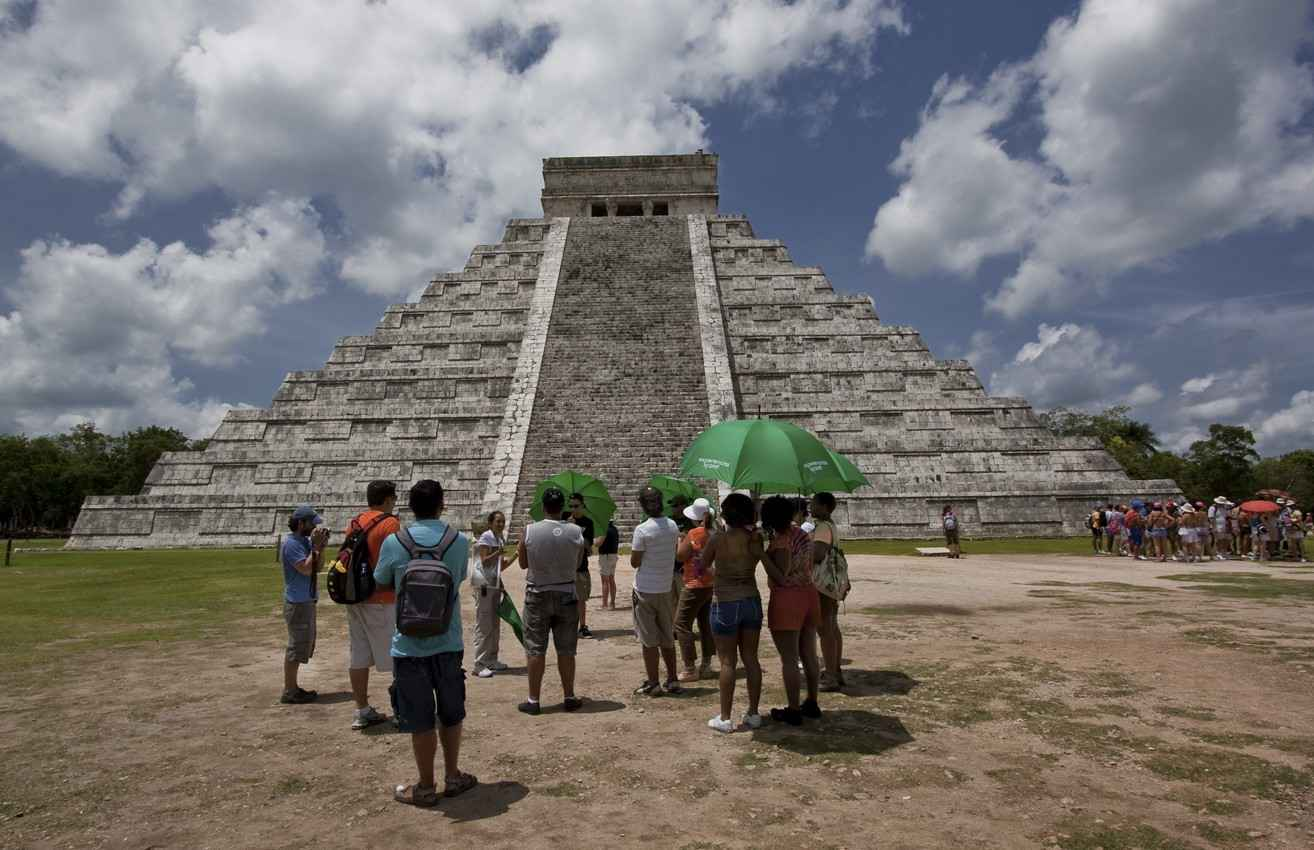 Another group of tourists standing in front of the large pyramid El Castillo.