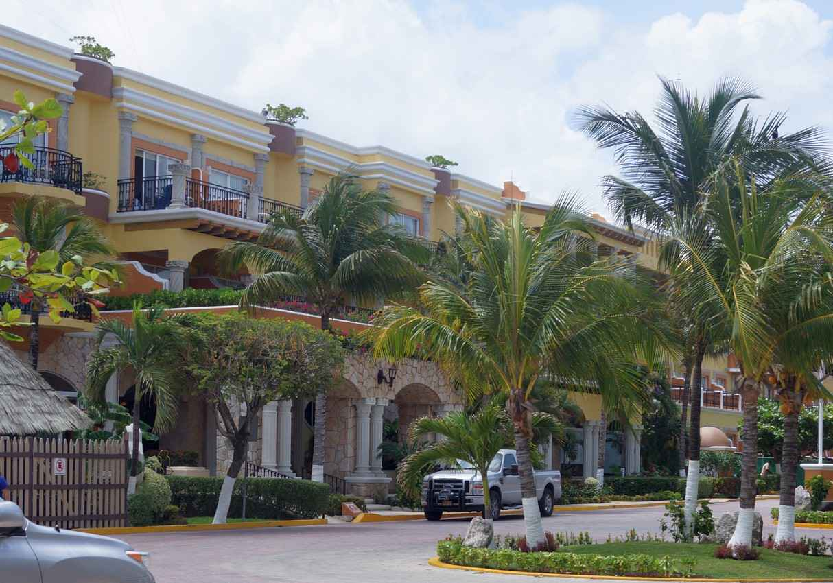 A yellow condo hotel near the beach in Playa Del Carmen.
