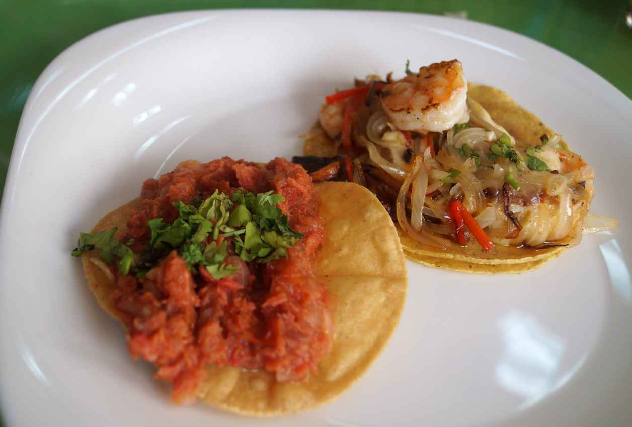 A pork taco next to a seafood taco with both served on soft corn tortillas.