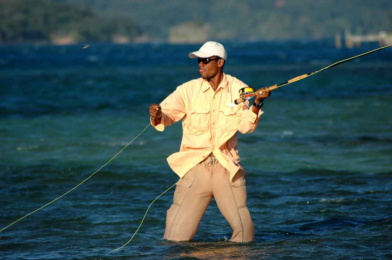 A man fly fishing in a bay in the Caribbean.