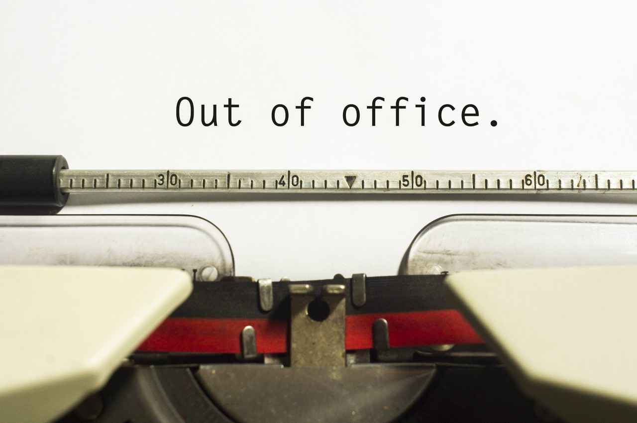 A piece of paper in a typewriter with, out of office, written on it.