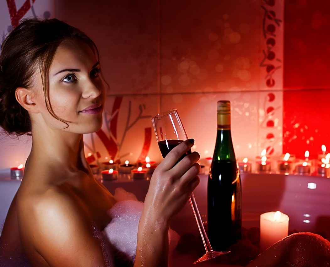 A beautiful woman drinking a glass of red wine while sitting in a private resort Jacuzzi.