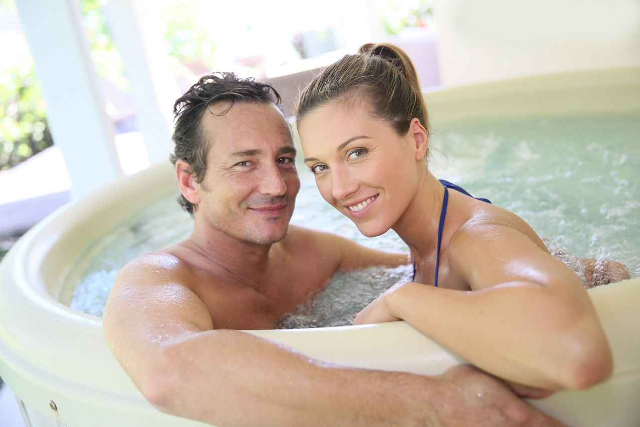 An average man and a sexy woman taking a Jacuzzi bath on their honeymoon.