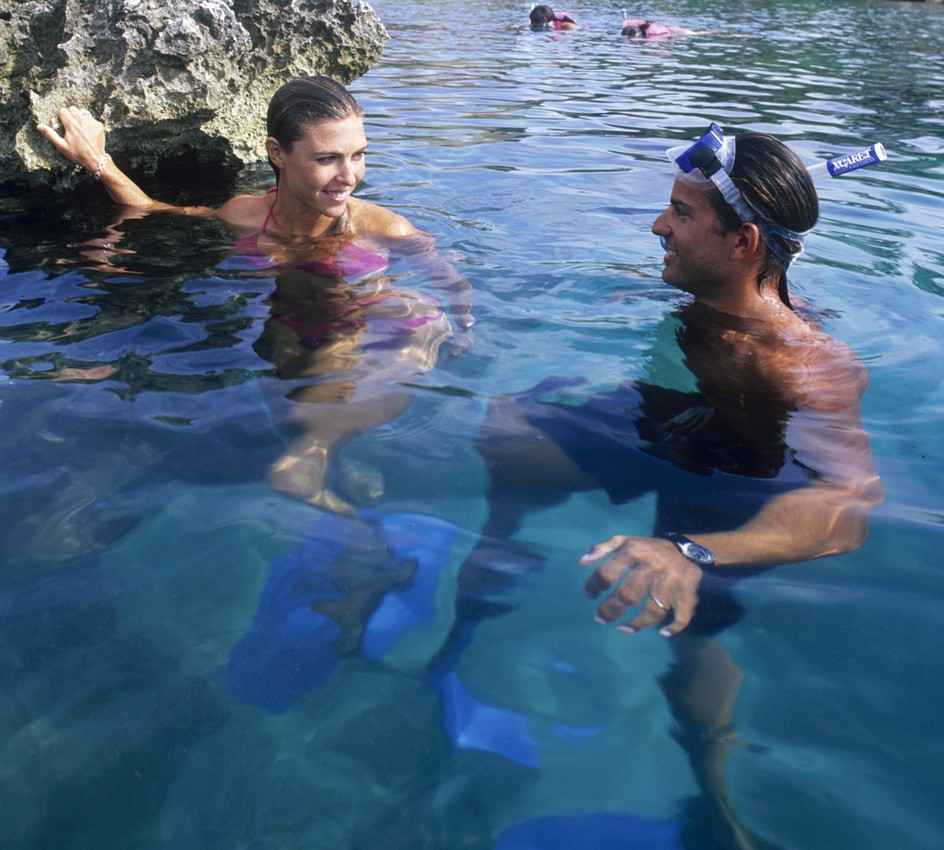 A man and a woman who are celebrating their honeymoon snorkeling together.