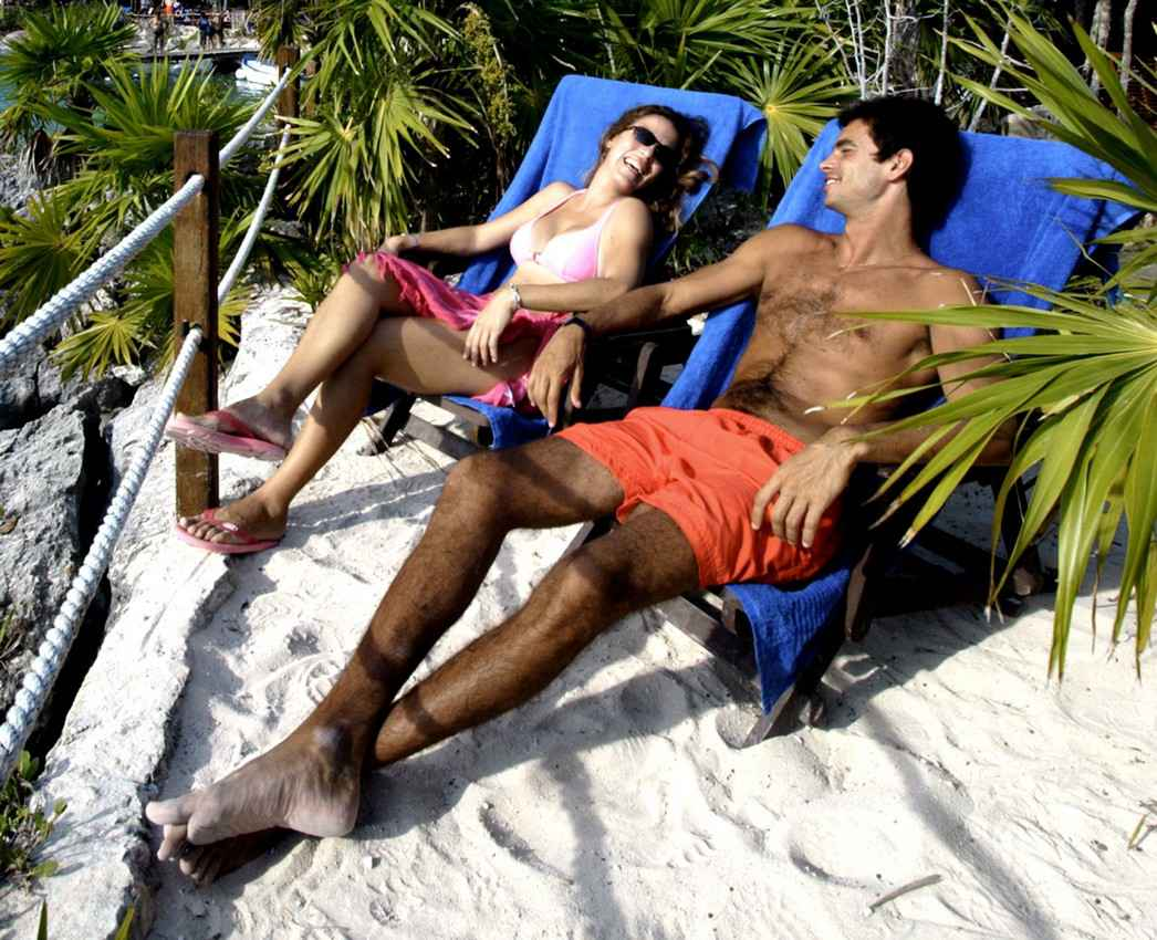 A romantic couple sitting in lounge chairs near the beach and the jungle.
