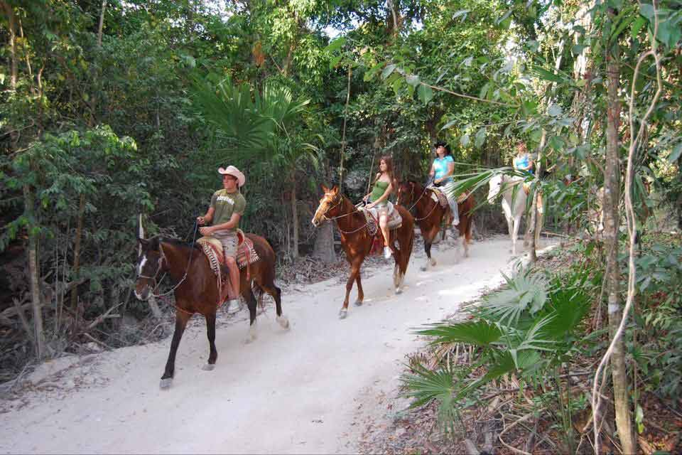 Three women and a guide riding horses through the Playa Del Carmen jungle