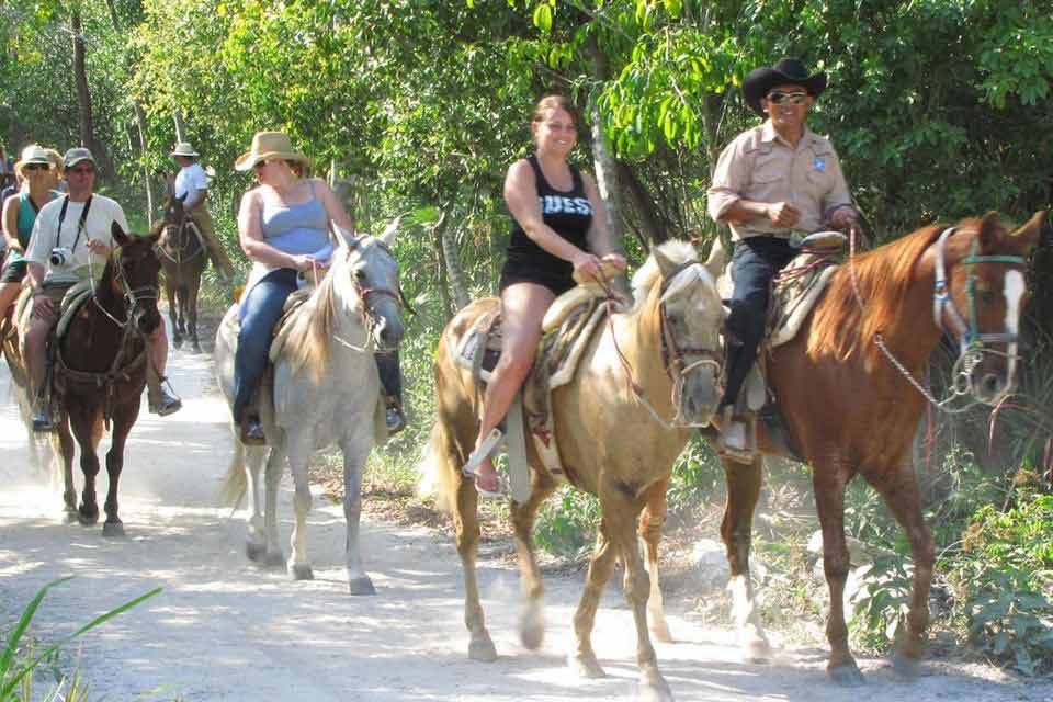 A cool-looking tour guide leading a group of people on horses in jungle horse riding activity