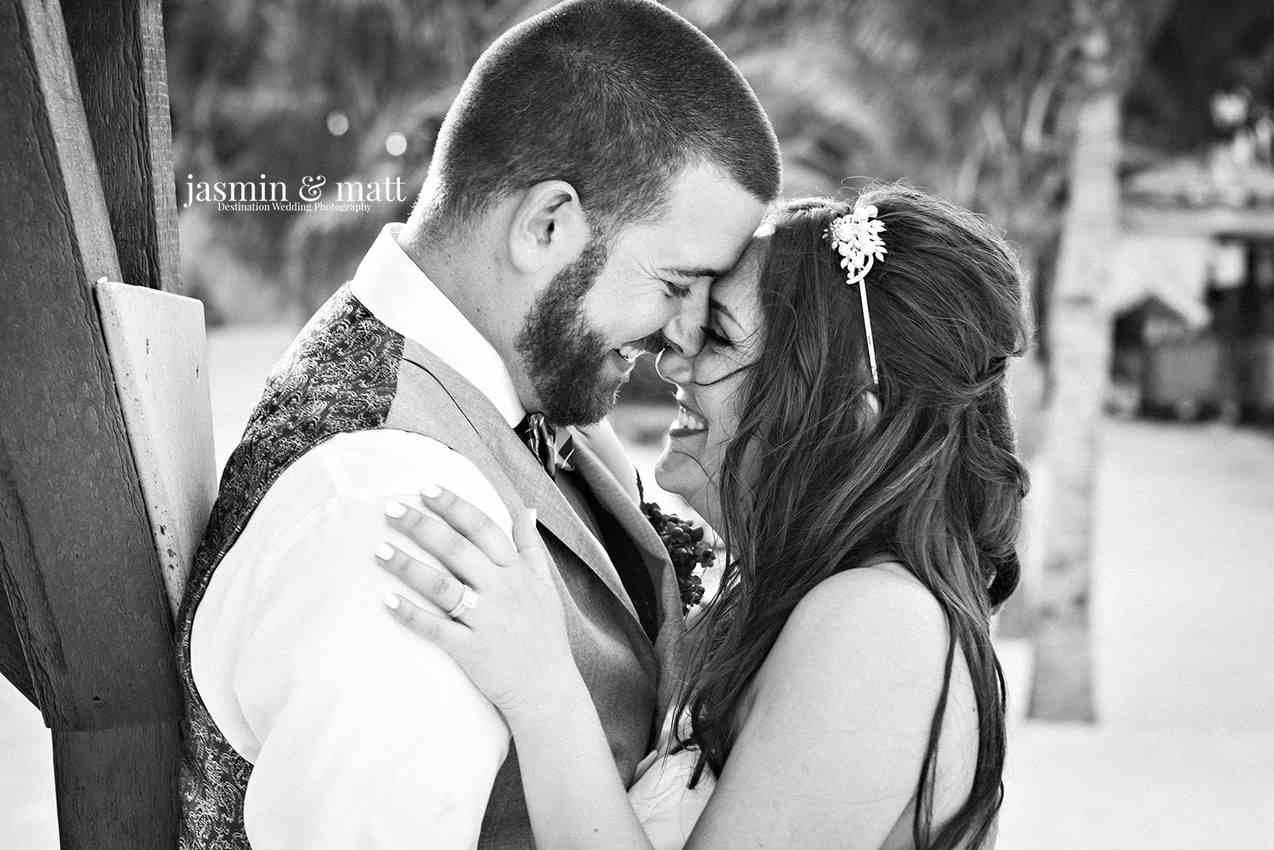 A black and white picture of a bride and groom kissing near some trees.