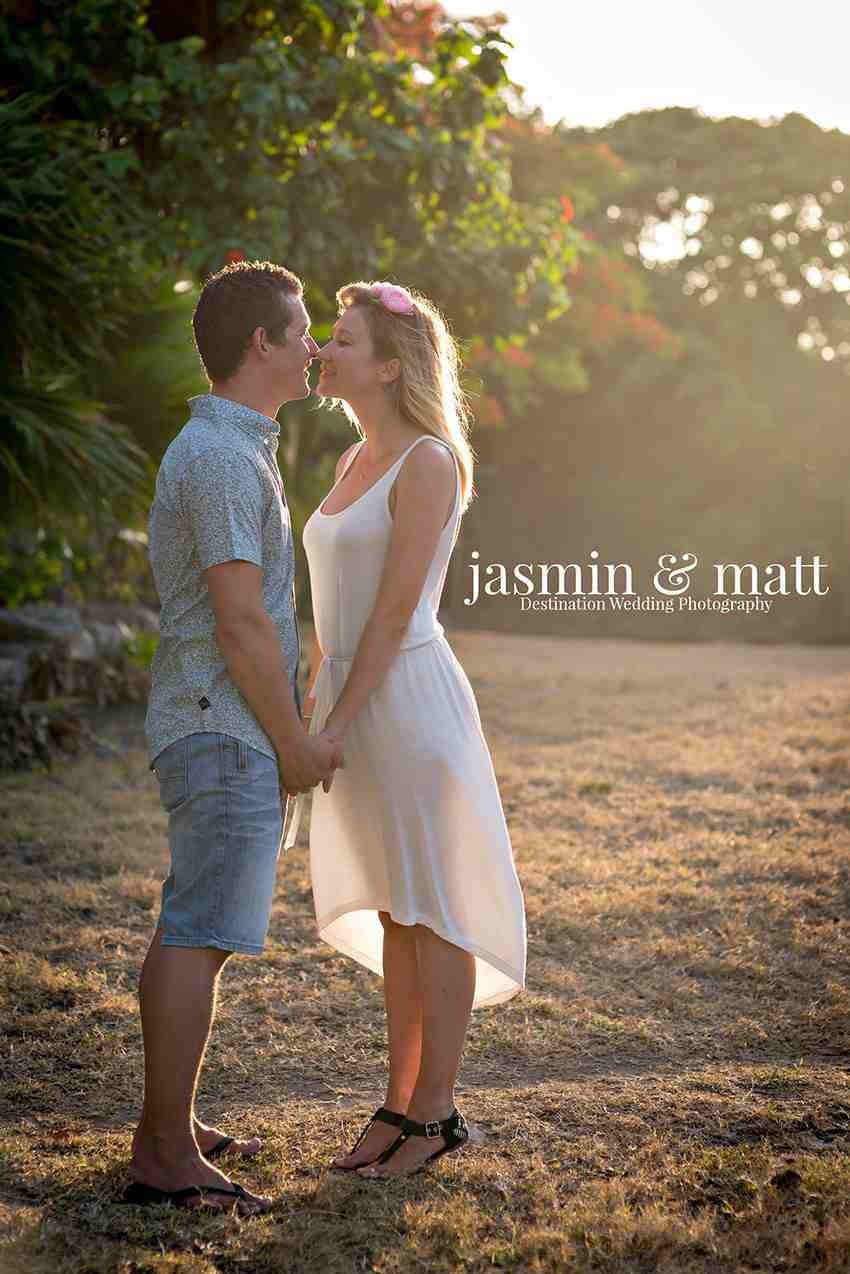 A couple kissing in front of a forest with sun shining on them.