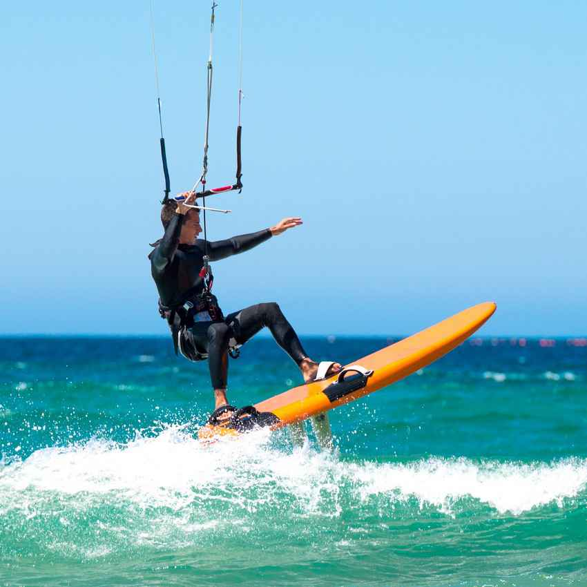 A man on a kite board doing an aerial jump over a wave.