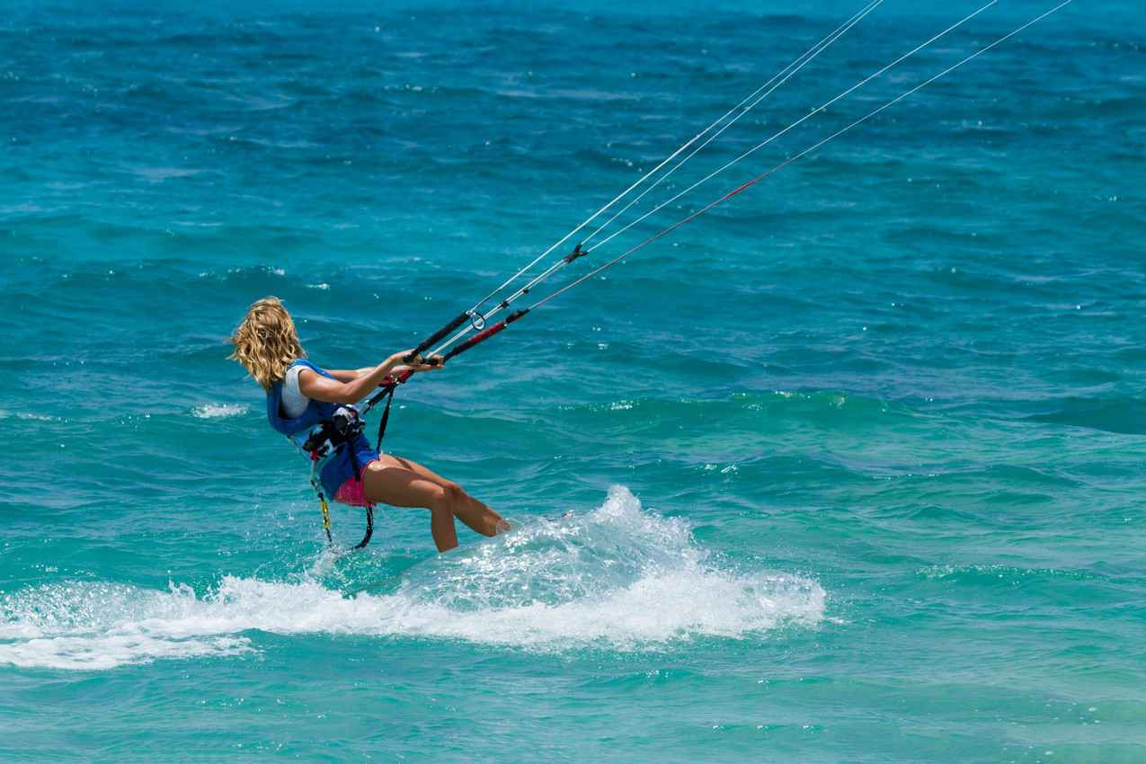 A very strong woman kite boarding in rough waters.