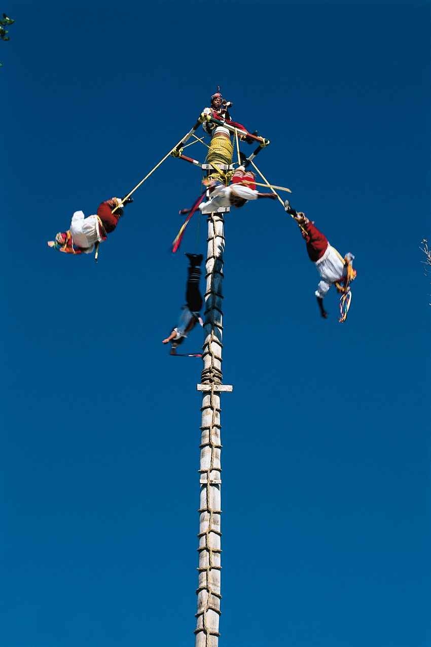 A group of traditional flying men at the top of a pole during a demonstration.