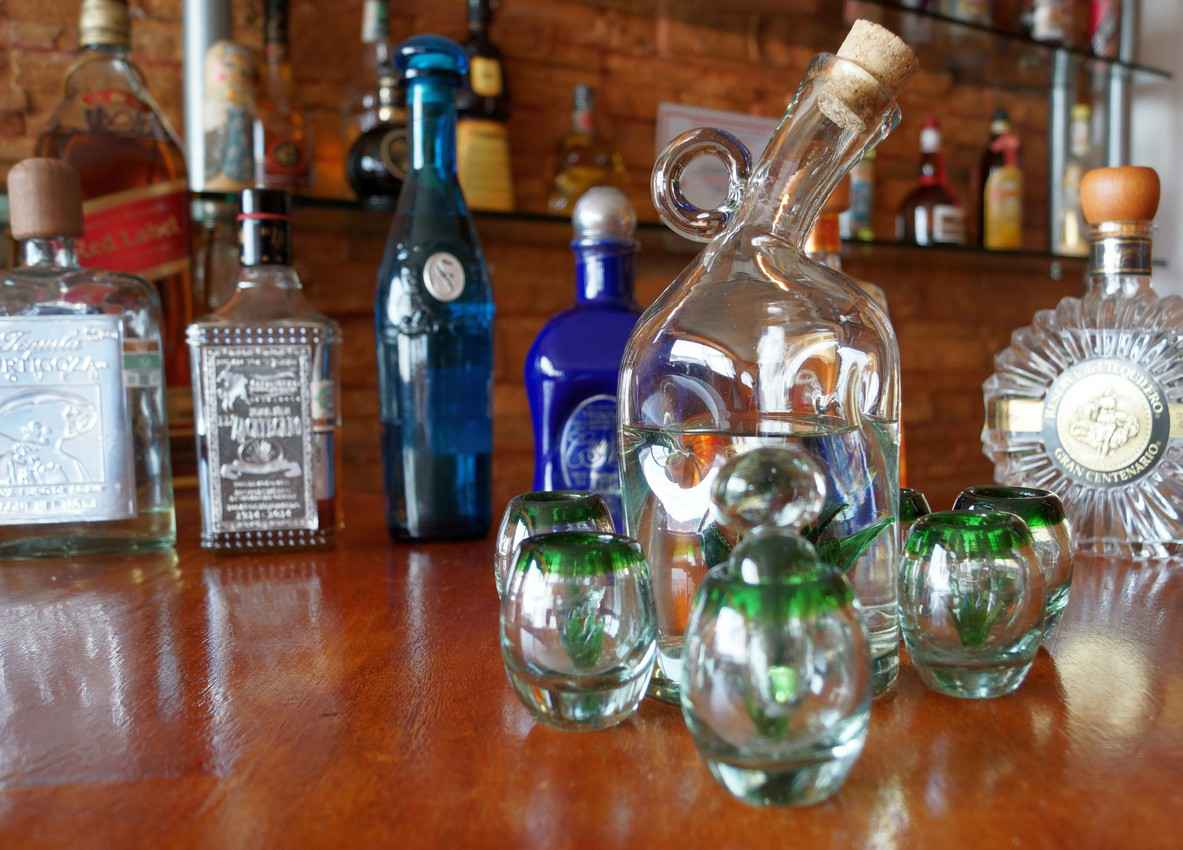 A group of several different beautiful tequila bottles lined up on a bar.
