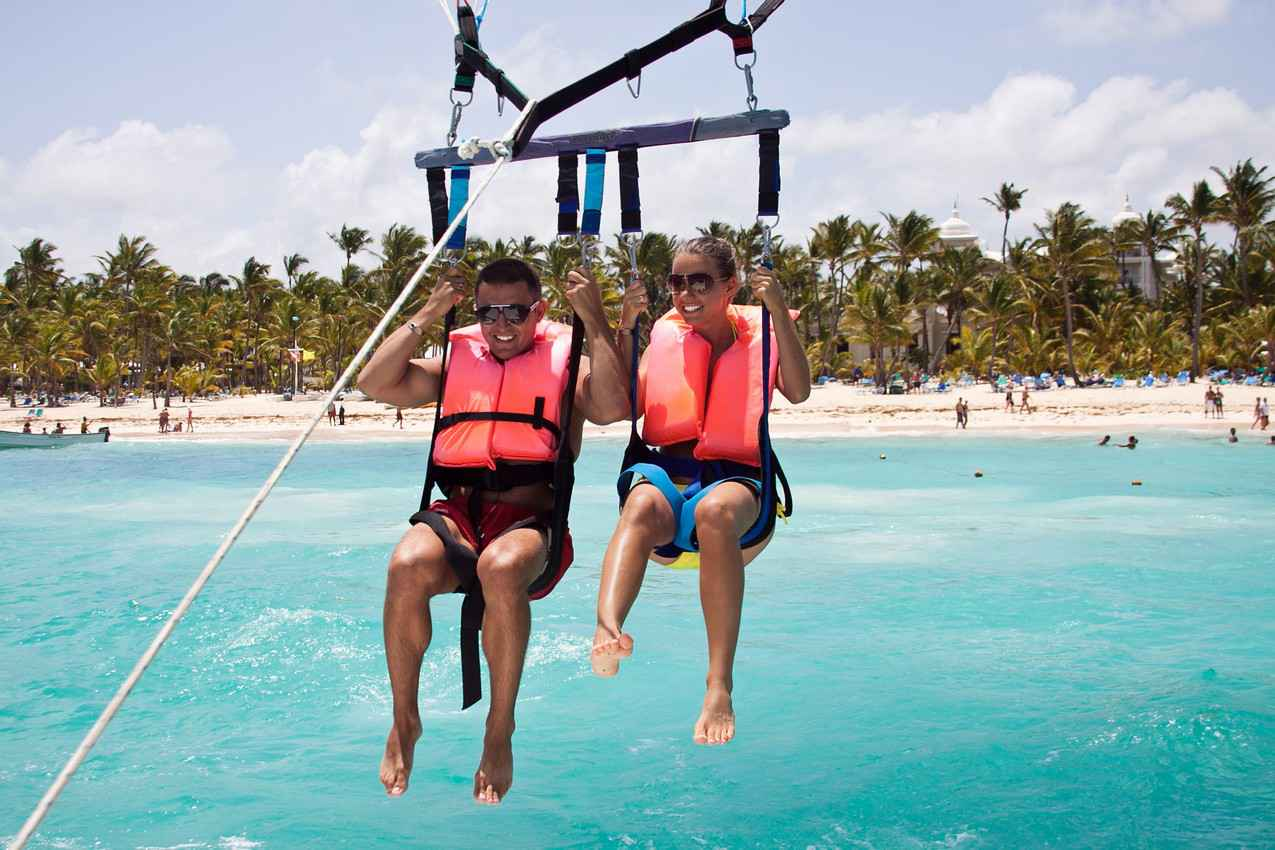A newlywed couple parasailing close to the beach in Playa Del Carmen.