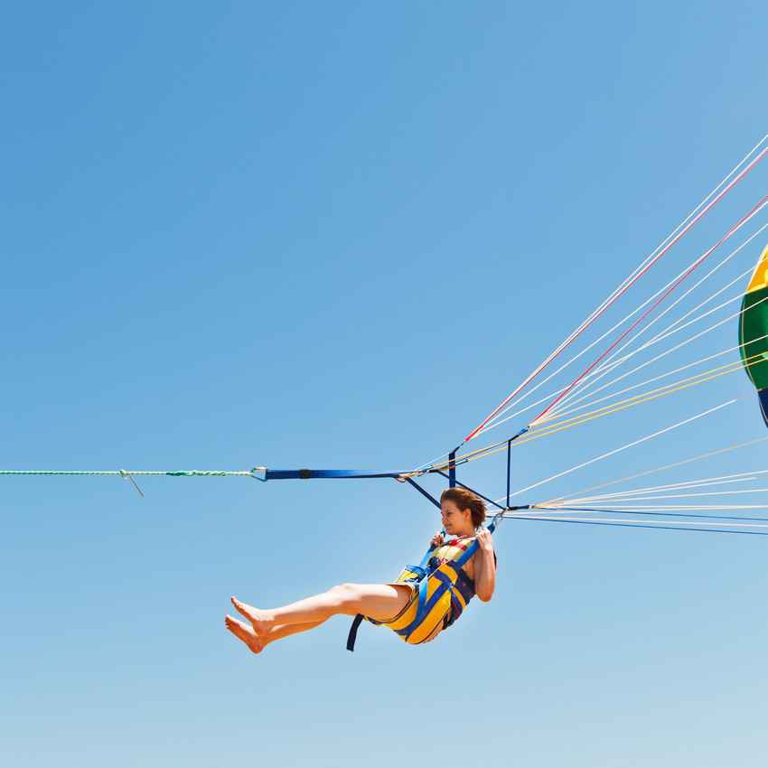 A woman hanging from a parasail.