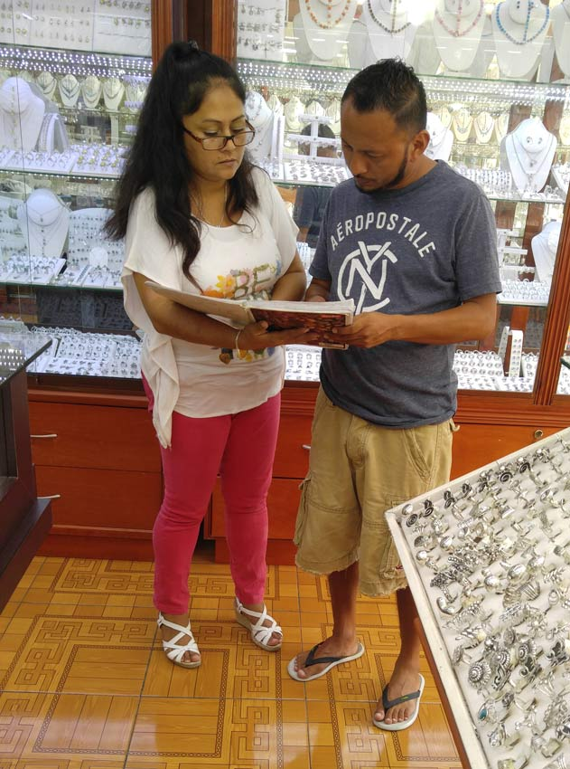 Chino and his assistant from Lahuella Del Oso looking at their sale records.