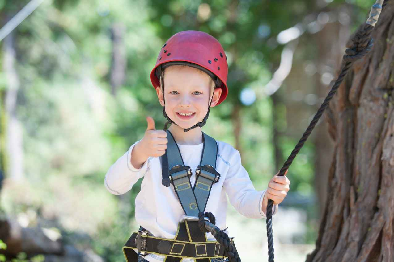 A smiling young boy who is ready to go zip lining wearing a helmet and a safety harness.
