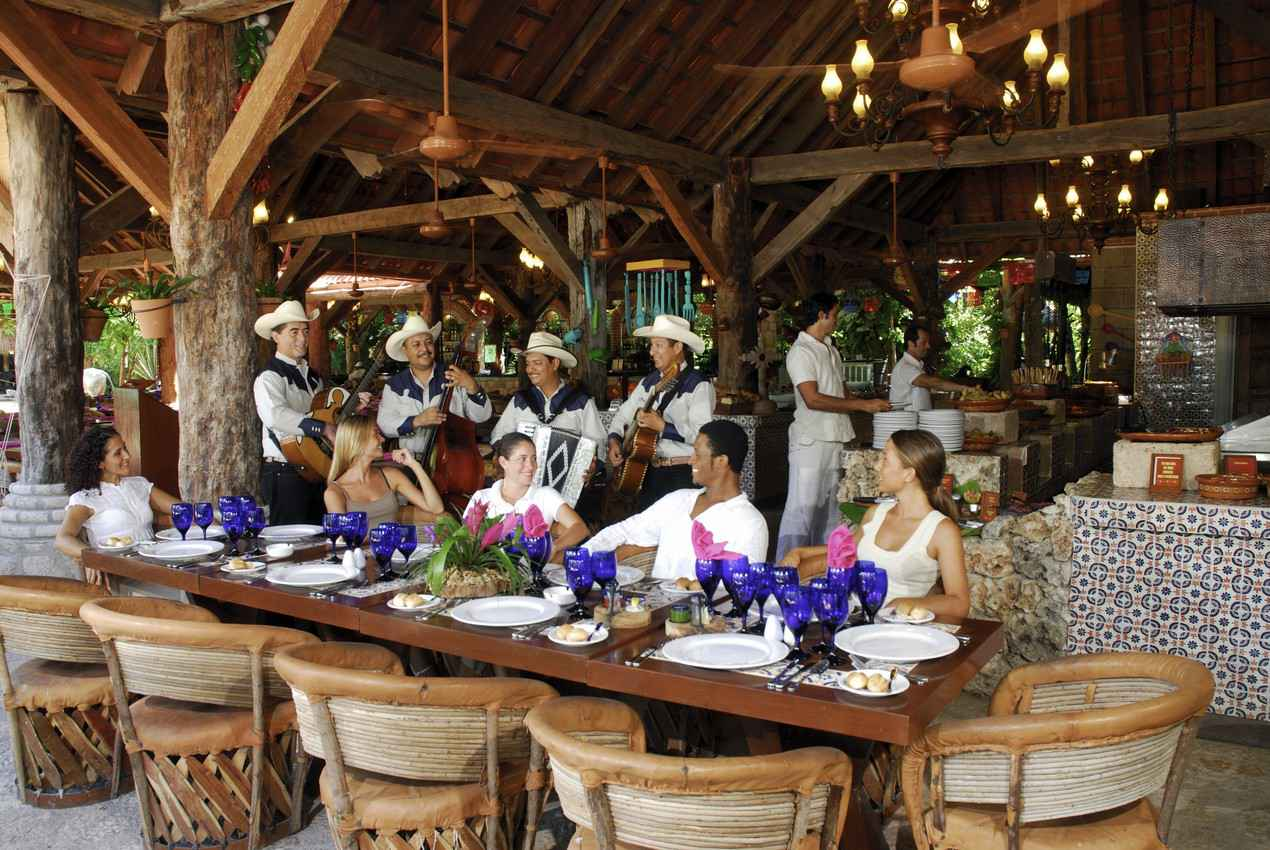 A group of four men playing boring Mexican music at a resort restaurant.