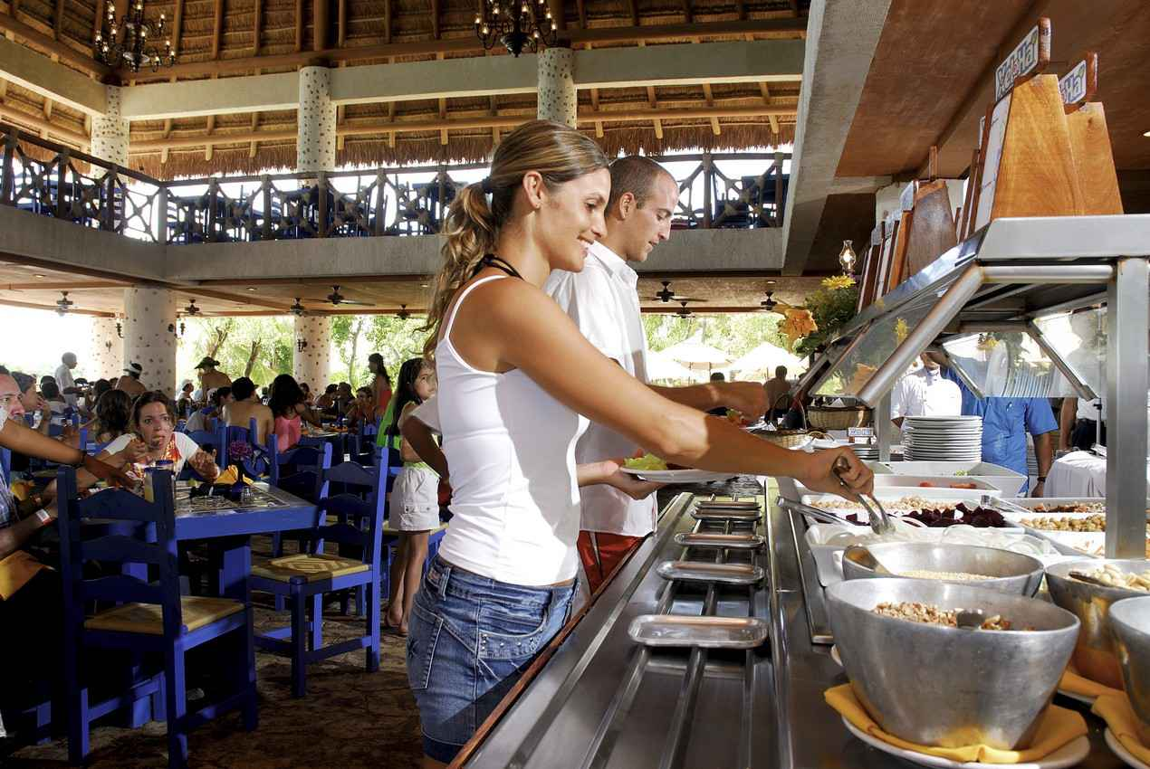 A man and a woman serving themselves breakfast cereal at an all-you-can-eat buffet.