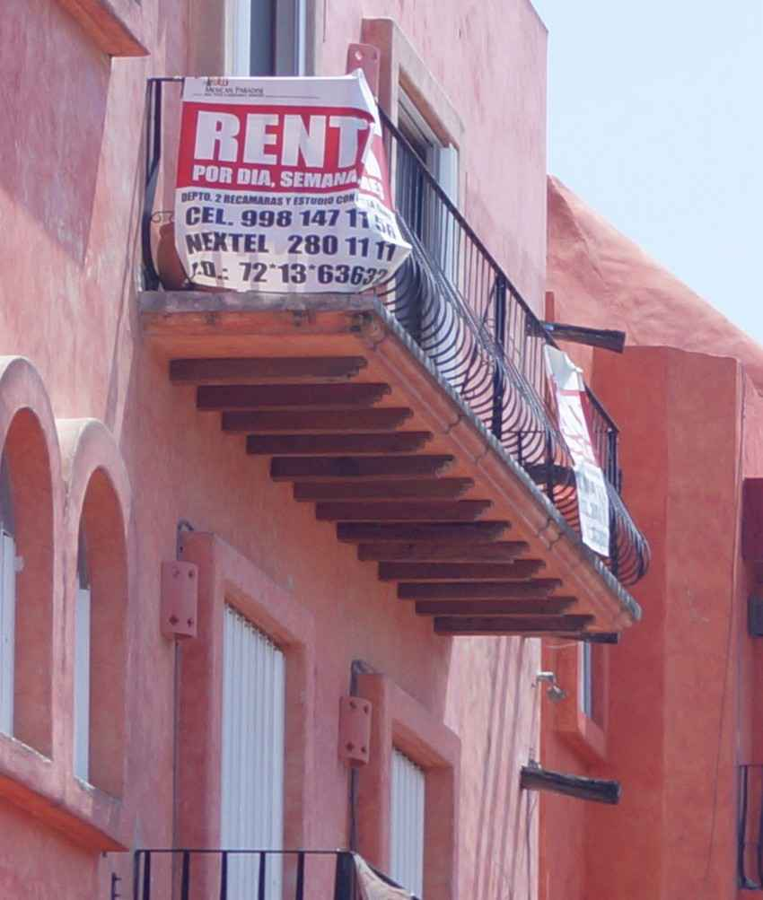 An apartment in downtown Playa Del Carmen with a FOR RENT sign hanging from the balcony.