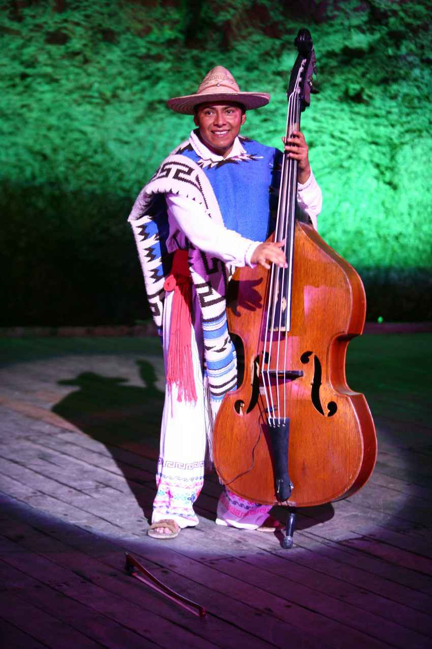 A performer dressed in traditional Mexican attire playing a cello at a local event.