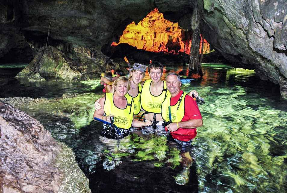 A family posing for a picture in a cave seen during an ATV activity in Playa Del Carmen