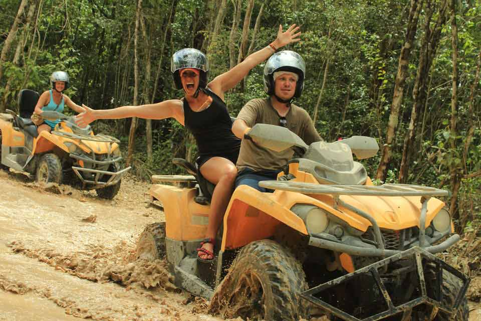 A man and woman driving an ATV through a jungle swamp near Playa Del Carmen