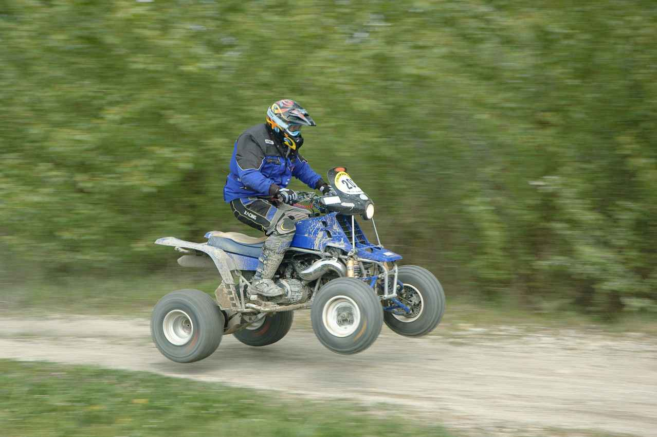 A man riding a blue ATV on a back road in Playa Del Carmen.