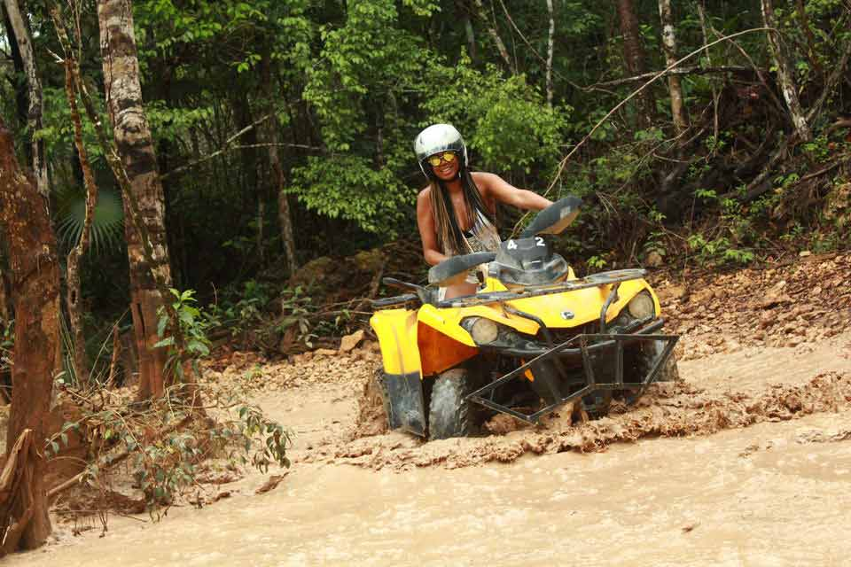 A woman driving an ATV through some deep mud in Playa Del Carmen