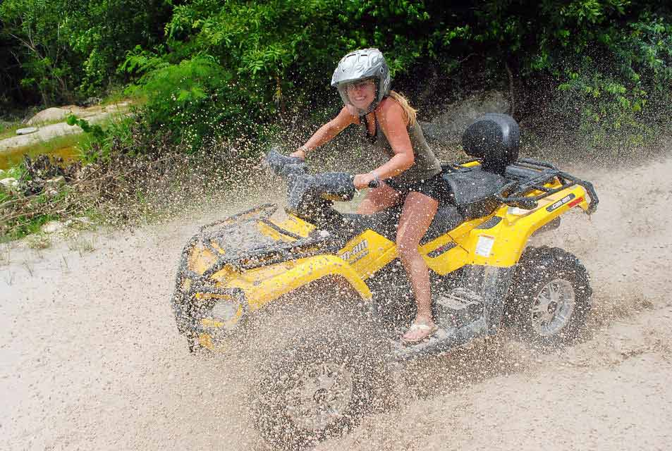 A woman riding an quad through a puddle in the jungle near Playa Del Carmen