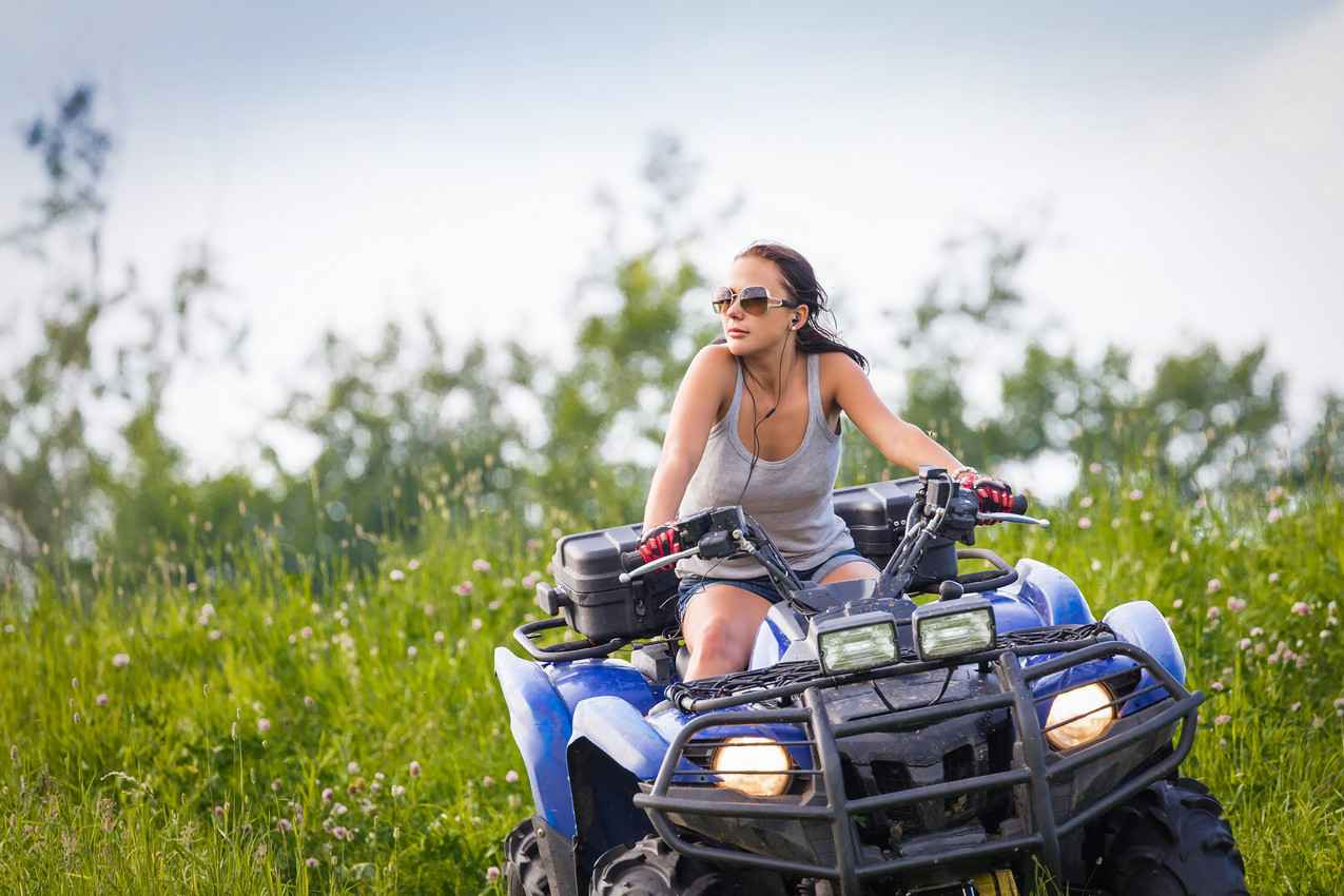 A woman riding an ATV and listening to music at the same time.