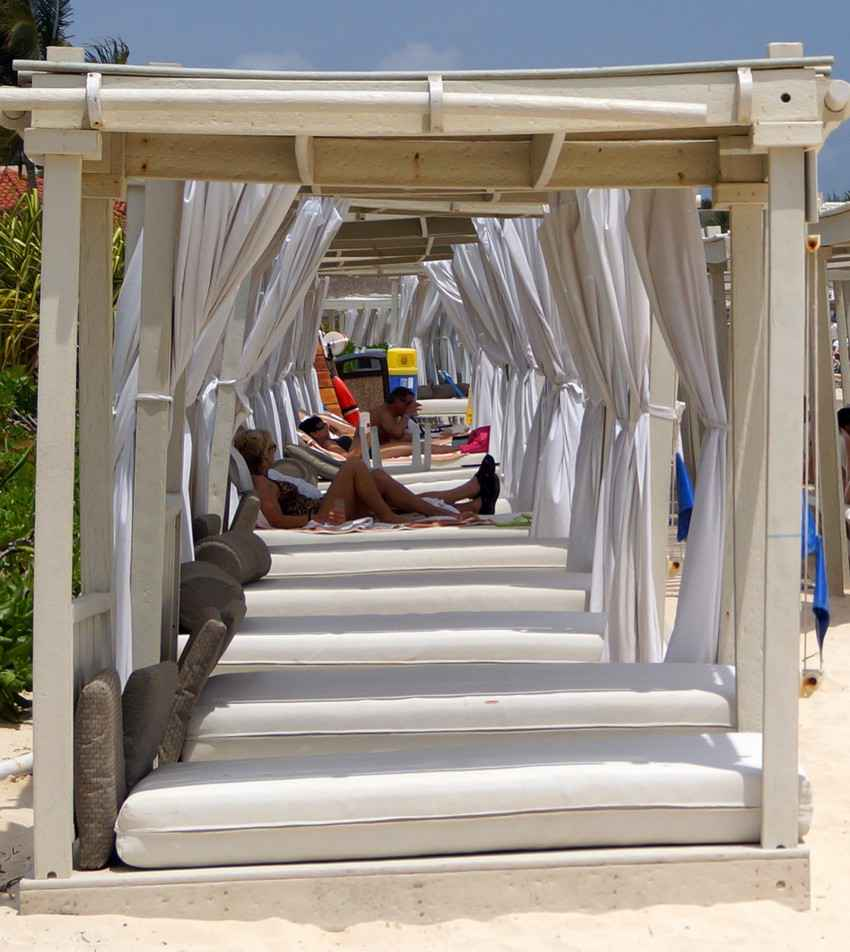 A row of beach beds for rent outside of a beach club in Playa Del Carmen.