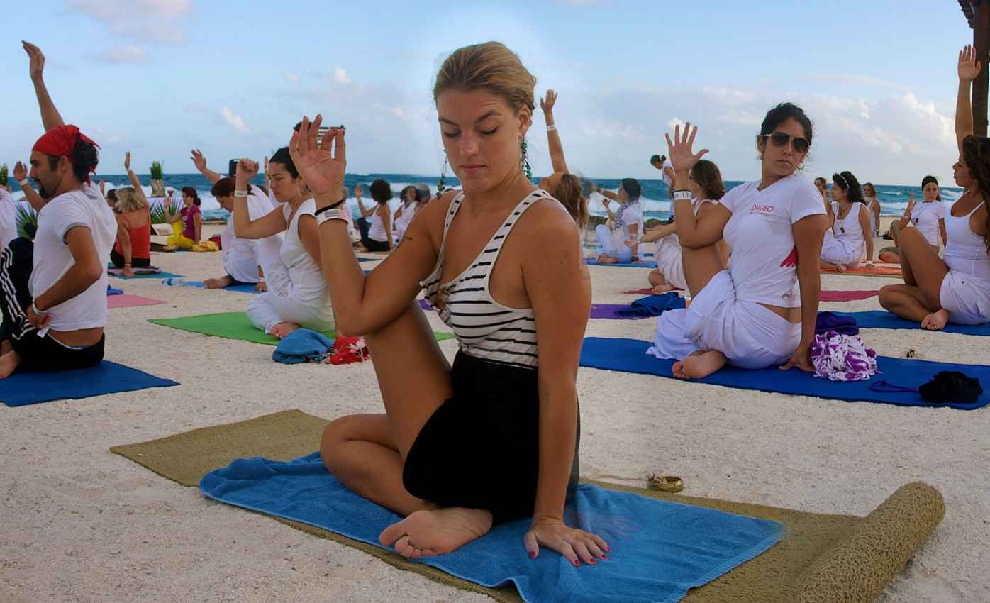 A large group of people doing yoga on the beach.