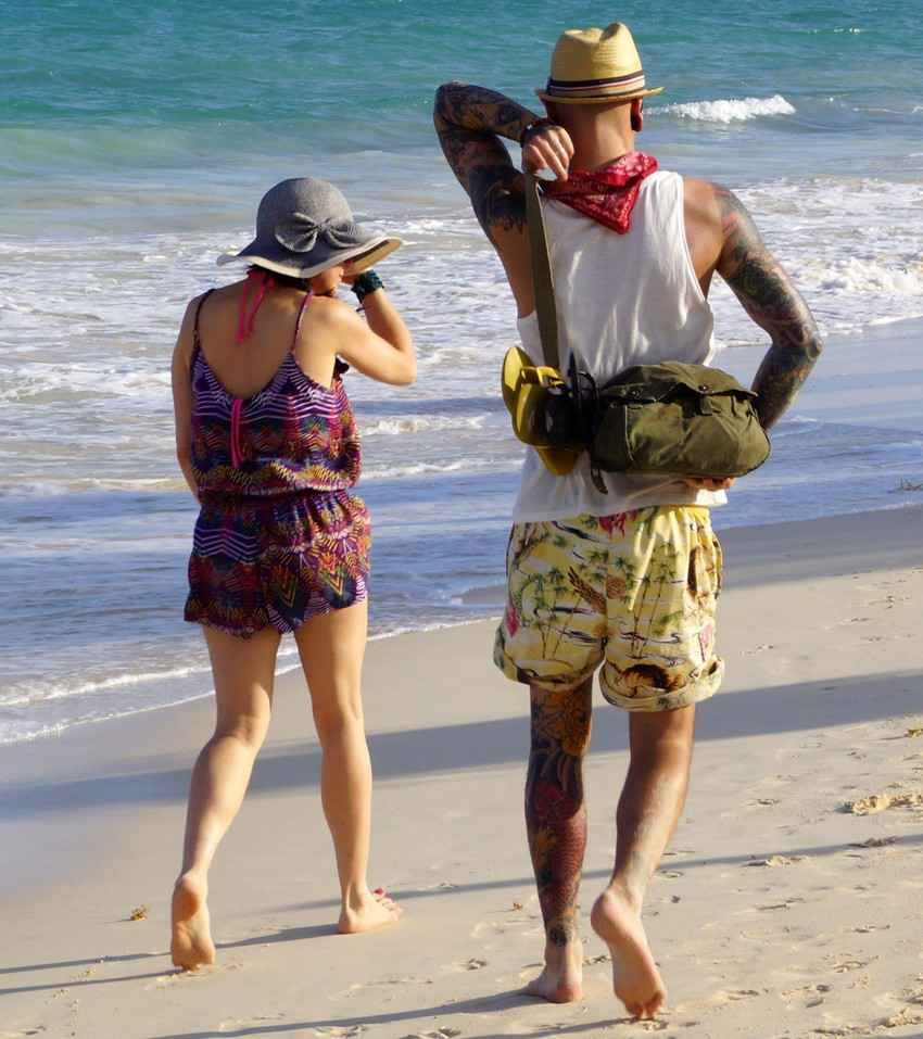 A man and a woman with a lot of tattoos walking on the beach.